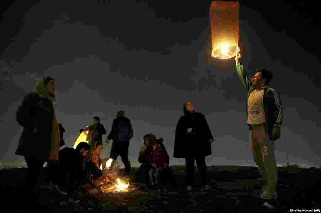 "An Iranian man releases a lit lantern during a celebration, known as ""Chaharshanbe Souri,"" or Wednesday Feast, marking the eve of the last Wednesday of the solar Persian year, Tuesday, March 19, 2019 in Tehran, Iran."