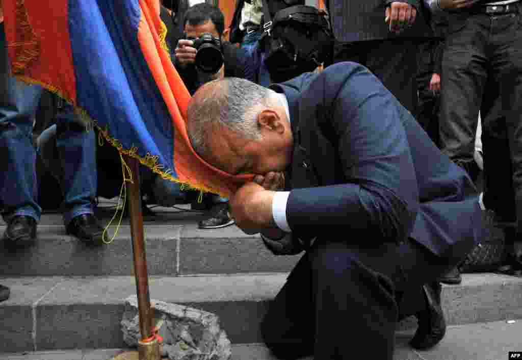 Raffi Hovannisian kisses an Armenian flag during the opposition rally.
