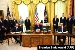 Президент Сербии Александр Вучич (слева) и премьер-министр Косова Авдулла Хоти (справа) на церемонии подписания экономического соглашения в Вашингтоне в присутствии президента США Дональда Трампа (в центре)