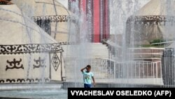 Мальчик на фоне фонтанов и юрт на площади Ала-Тоо в Бишкеке. 31 августа 2020 года.