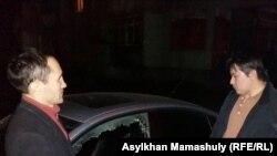 Активист Жанболат Мамай (справа) заявляет, что его машина была преднамеренно повреждена, Алматы, 6 декабря 2016 года.