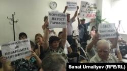 Гражданские активисты во время общественных слушаний держат плакаты против повышения цен за свет. Уральск, 13 августа 2015 года.