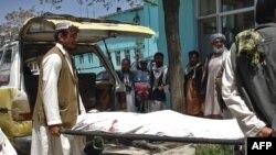 چند شهروند محلی در حال انتقال جسد یکی از کشتهشدگان در انفجار روز یکشنبه در غزنی
