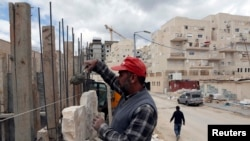 کارگر فلسطینی در حال کار در شهرک یهودینشین در نزدیکی اورشلیم