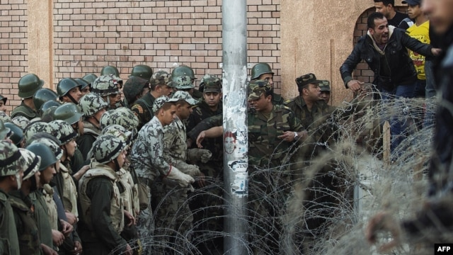 Egyptian soldiers prevent demonstrators from crossing over a barbed-wire fence as thousands gather near the presidential palace in Cairo to protest against a draft constitution and President Muhammad Morsi's sweeping decree.