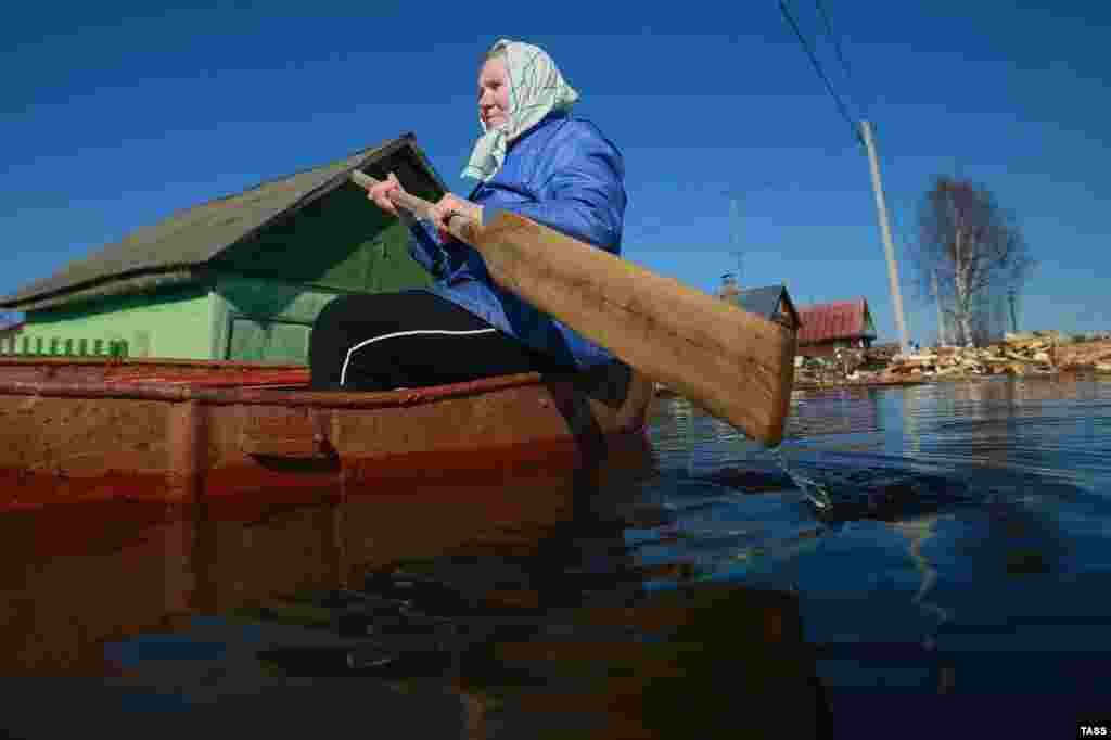 An elderly woman paddles a small boat on a flooded street in the Russian village of Kholui in the Ivanovo region. (TASS)