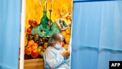 Медработник в защитной одежде в пункте вакцинации