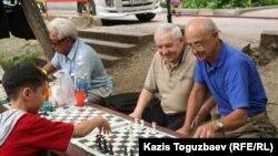 """11-летний Досбулат Жупархан """"во дворе дяди Казиса"""" играет в шахматы с мастером спорта по шахматам Александром Синявским (рядом с ним любитель игры в теннис и шахматы Анатолий Авдеев). Алматы, 6 июня 2010 года."""