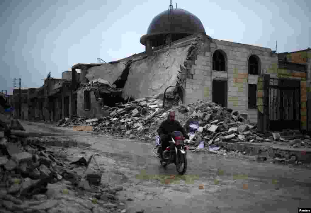 A man rides a motorcycle past a mosque destroyed by a government air strike in Syria's Azaz city. (Reuters/Ahmed Jadallah)