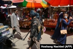 A Taliban fighter walks past shoppers at the Mandawi market in Kabul on September 1.