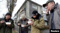 Ставропольде үйсіз адамдар тегін берілген түстік ас ішіп тұр, Ресей (Көрнекі сурет).