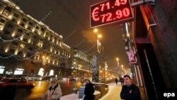 Люди проходят мимо пункта обмена валют в Москве. 15 декабря 2014 года.