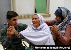 Relatives of the victims mourn at a hospital after a suicide attack in Kabul on June 11.