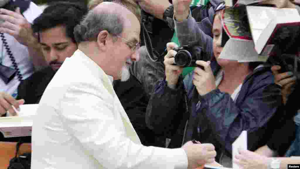 "Rushdie signs autographs as he arrives for a festival showing in Toronto, Canada, in September 2012 of the film ""Midnight's Children,"" based on his Booker Prize-winning book from 1981."