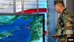 Сирия армиясы өкілі түрік ұшағы құлады деген маңды картадан көрсетіп тұр. Сирия, 23 маусым 2012 жыл. (Телеарна бейнежазбасынан жасалған скриншот)