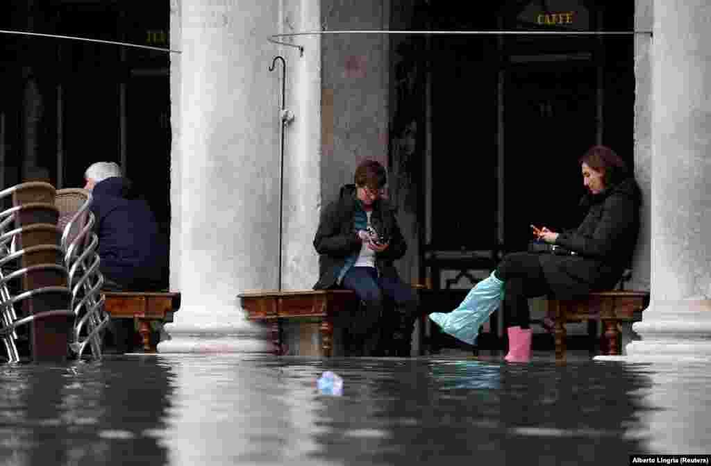 Люди сидять біля кафе під аркадами на площі Святого Марка