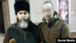Said Mazhayev (right), a Chechen who returned home purportedly after six months fighting in Syria and was touted in Russian media as a repentant former Islamic State (IS) militant, shown with a Chechen mufti.