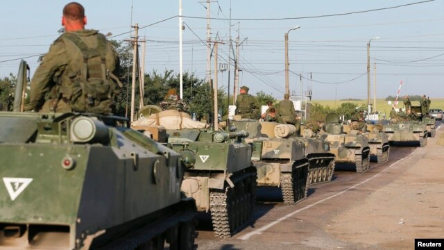 Russian military personnel sit atop armored vehicles outside Kamensk-Shakhtinsky in Russia's Rostov region on August 15.