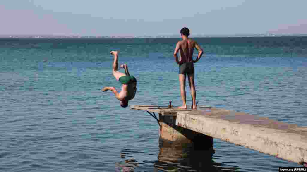 Молодежь и взрослые ныряльщики, несмотря на то, что вода тут часто пахнет сероводородом, выстраиваются в очередь, чтобы сделать сальто в воду