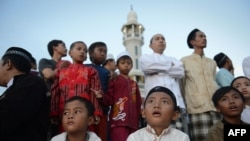 Indonesian children and elder Muslim men prepare to sight the new moon from the rooftop of the Al-Hidayah Basmol Mosque in Jakarta on July 8.