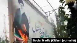 A billboard with a big picture of Supreme Leader Ali Khamenei, set on fire in the recent protests in Iran. November 16, 2019