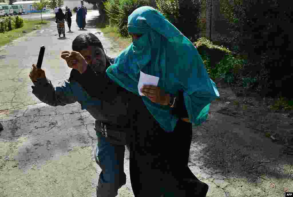 An Afghan police officer beats a woman as she waits for a food donation during the month of Ramadan in Kabul on August 1. (AFP/Shah Marai)