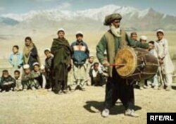 Elderly Afghan musician playing double-sided Afghan drum called a dhol.
