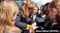 Акцияға келгендер көшедегі адамдарға сары лента таратып жатыр. Теміртау, 26 мамыр 2012 жыл.
