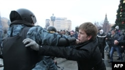 Soccer fans clash with riot police in central Moscow on December 11.