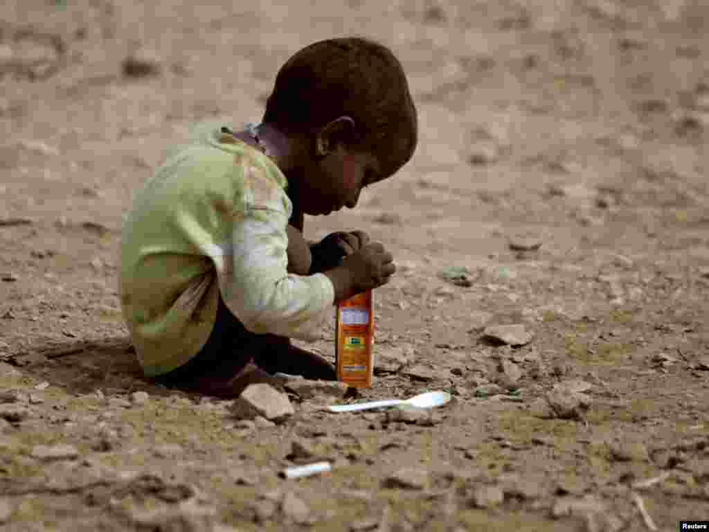 A child, displaced for a year by Pakistan's deadly flooding, plays with an empty juice box outside his family tent while taking refuge along a road in Jamshoro, north of Karachi, on July 25. Photo by Akhtar Soomro for Reuters