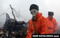 Rescuers wear protective gear while working at the crash site on January 16.