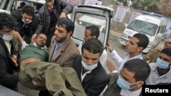Medics carry an injured antigovernment protester into a makeshift clinic in Sanaa on March 13.