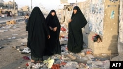 Iraqi women gather at the site of a blast at the Mraidi market in Baghdad's Sadr City.