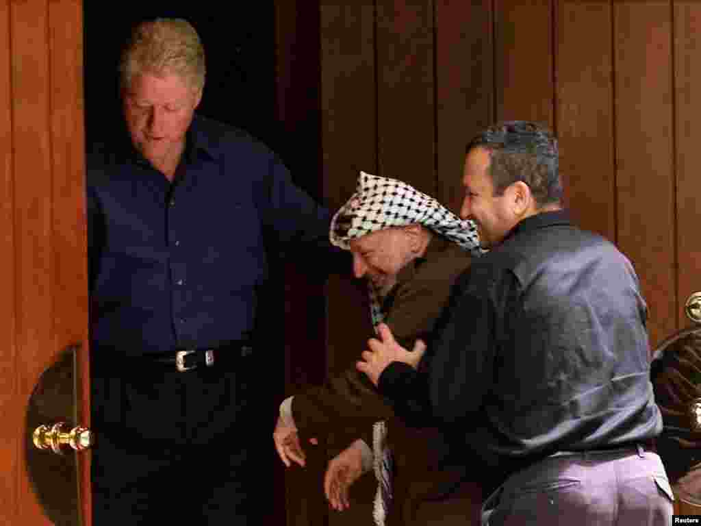 Israeli Prime Minister Ehud Barak (R) jokingly pushes Palestinian President Yasser Arafat (C) into the Laurel cabin on the grounds of Camp David as U.S. President Bill Clinton watches during peace talks, July 11, 2000. Arafat and Barak were insisting that the other proceed through the door first. Camp David is the venue where Egypt and Israel made peace in September 1978, and the Laurel cabin was the site of many of the meetings. REUTERS
