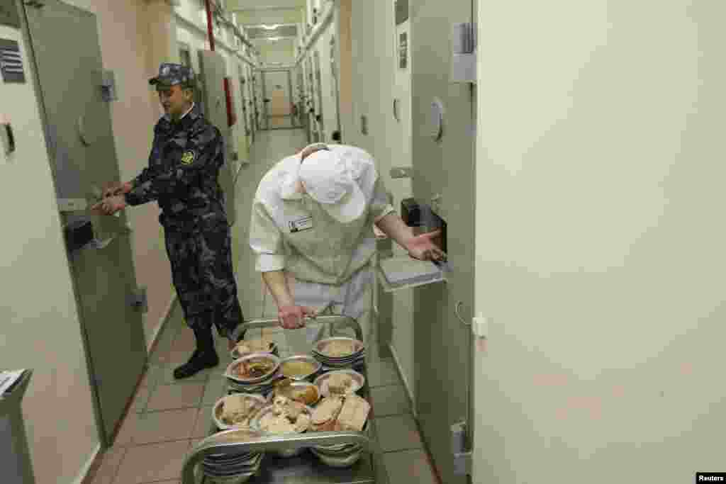 A security officer stands next to an inmate serving dinner to other prisoners inside a maximum-security zone.