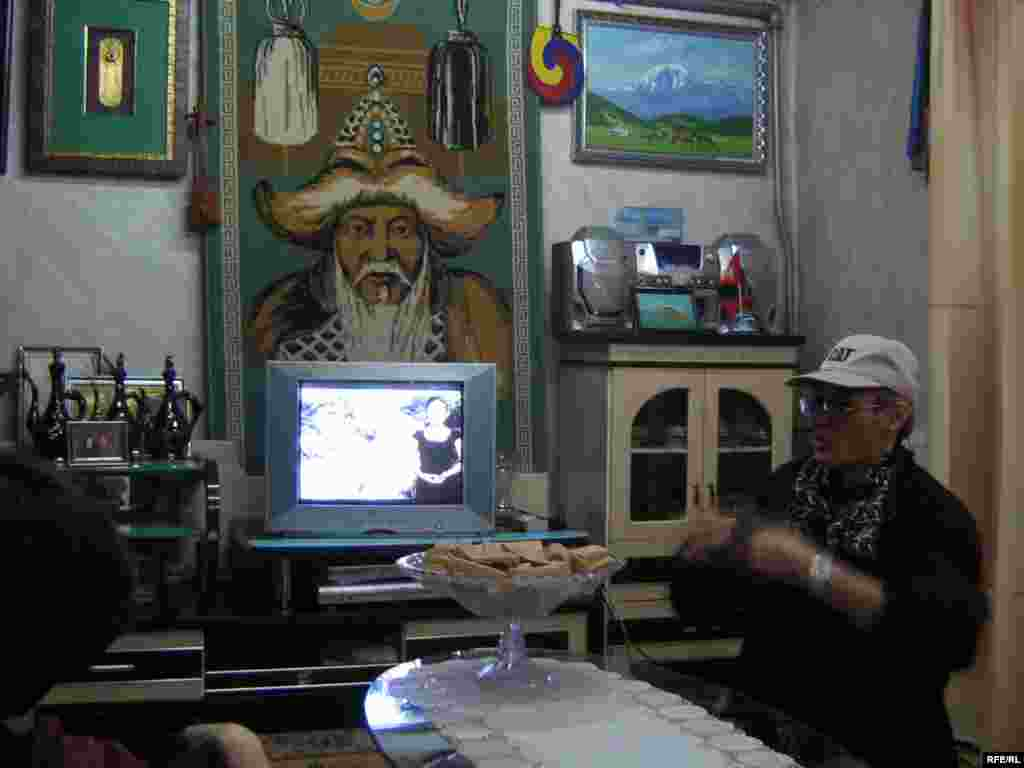 An image of Chinggis Khan adorns the wall of a private home in the village of Zuunkharaa. - Many Mongolian living rooms feature a must-have trinity of Chinggis Khan, a Buddhist shrine, and the obligatory bowl of aruul, or dried cheese curds.