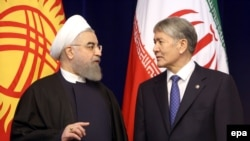 Iranian President Hassan Rohani (left) talks to Kyrgyz President Almazbek Atambaev during their meeting in Bishkek on December 23.