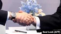 Birleşen Ştatlaryň prezidenti Donald Tramp (sagda) we rus prezidenti Wladimir Putin elleşip salamlaşýarlar.