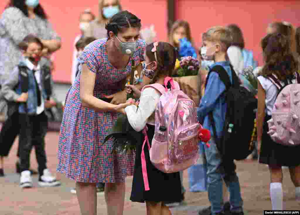A woman and a girl wearing protective face masks chat as they gather with teachers, parents, and other children in front of a school in the Romanian capital, Bucharest, on September 14 as classes started again after the summer break. ​Due to the coronavirus pandemic, most of Romania's schools reopened with students alternating between classroom learning and remote education.