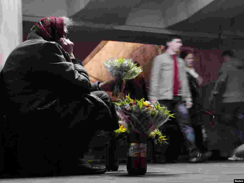 An elderly woman tries to sell flowers at an underground passageway in central Minsk. (Photo by Vasily Fedosenko for Reuters)