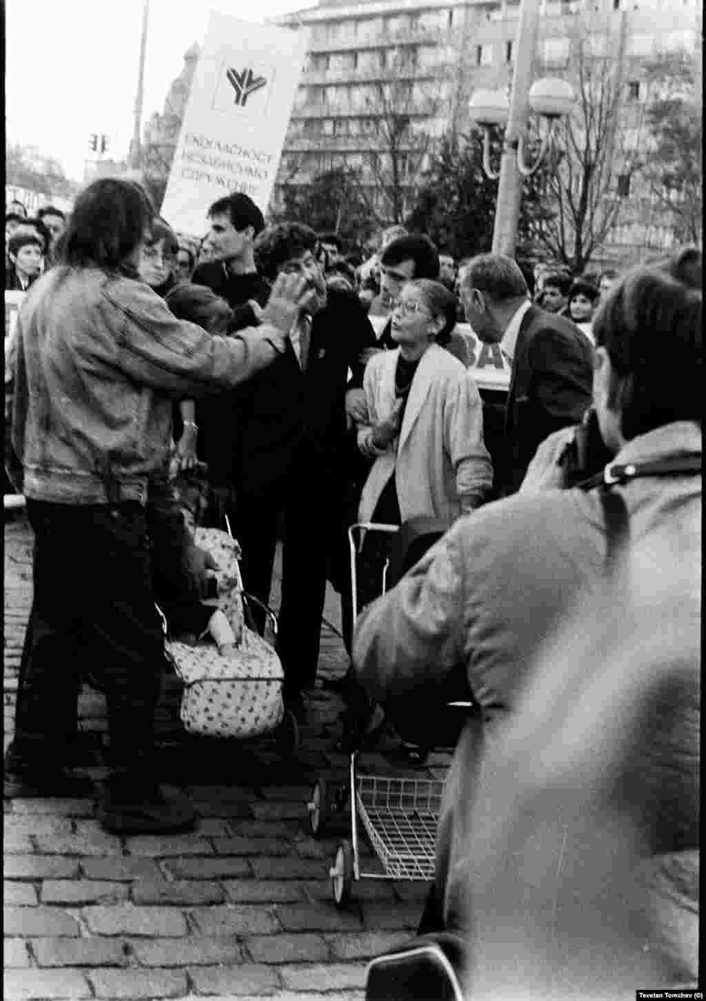Петър Слабаков и Петър Берон в разговор с млади жени, дошли за шествието заедно с бебетата си. По това време протестиращите майки с детски колички вече са се превърнали в емблема на съпротивата - през 1987 и 1988 г. те организират протести в Русе заради обгазяването на града, срещу което властите не взимат мерки.