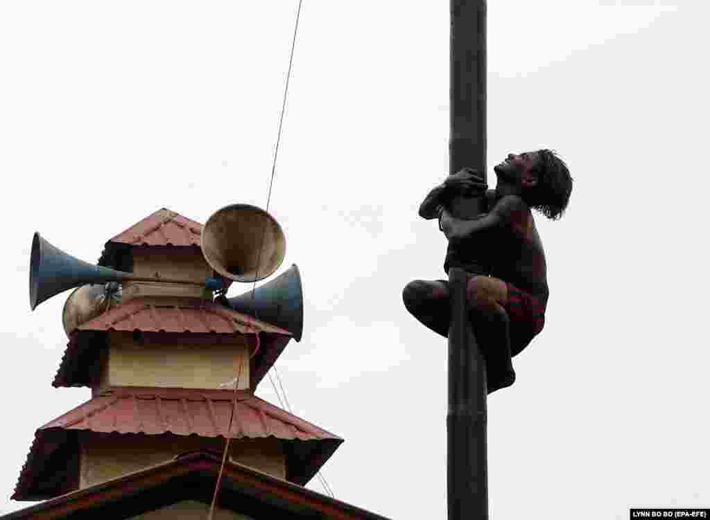 A Burma man tries to climb to the top of slippery bamboo pole, covered with lubricating oil, as he participates in a competition on the occasion of the 70th anniversary of Burma's Independence Day in Yangon. (epa-EFE/Lynn Bo Bo)