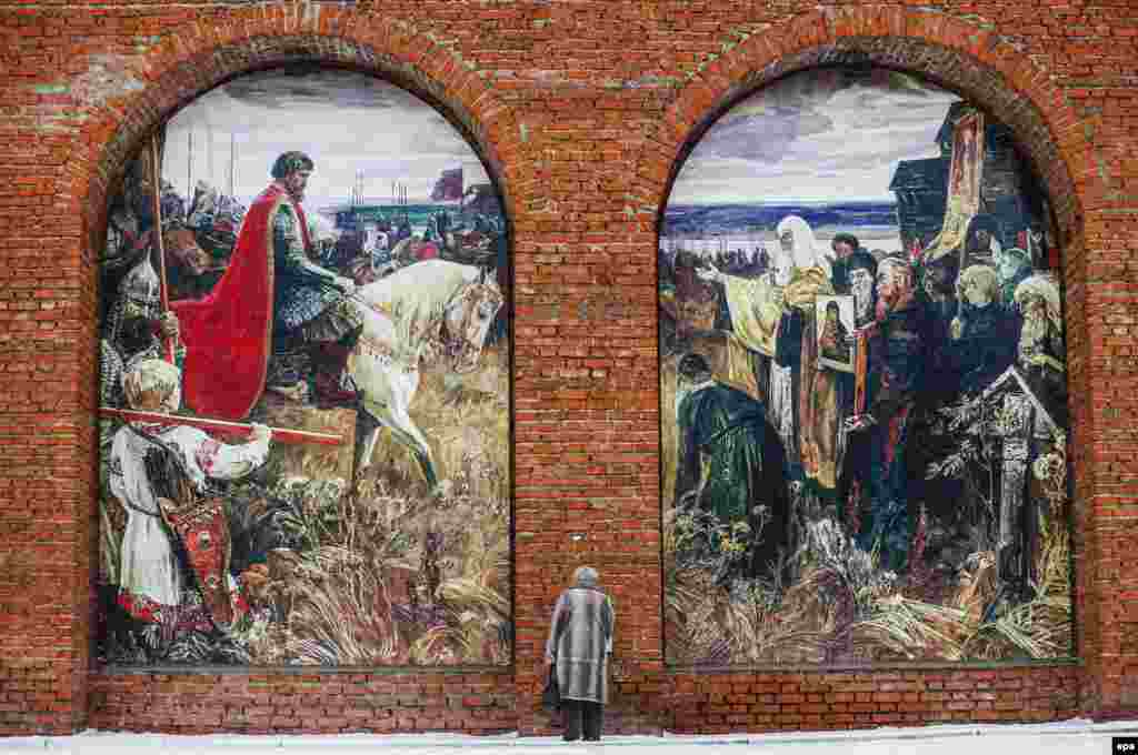 A Russian woman stands in front of the wall of the Kolomna Kremlin with huge painting of Dmitry Donskoy Assembles An Army Against The Tatars, in Kolomna, Russia. (epa/Sergei Ilnitsky)