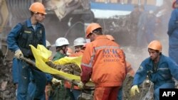 Rescuers remove the body of a victim from the site of September 9, 1999, bombing.
