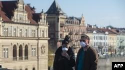 Люди в масках на Карловом мосту в Праге, 18 марта 2020 года.