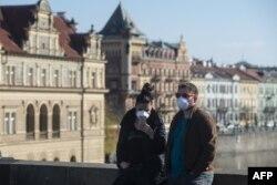 Чоловік та жінка у захисних масках стоять на Карловому мосту, Прага