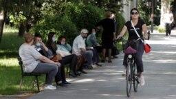 Žena na biciklu pored ljudi koji čekaju autobus, Podgorica, 25. maj, 2020.