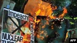 Protesters burn anti-North Korea placards with images of the North's leader, Kim Jong Il, during a protest in Seoul on May 25.