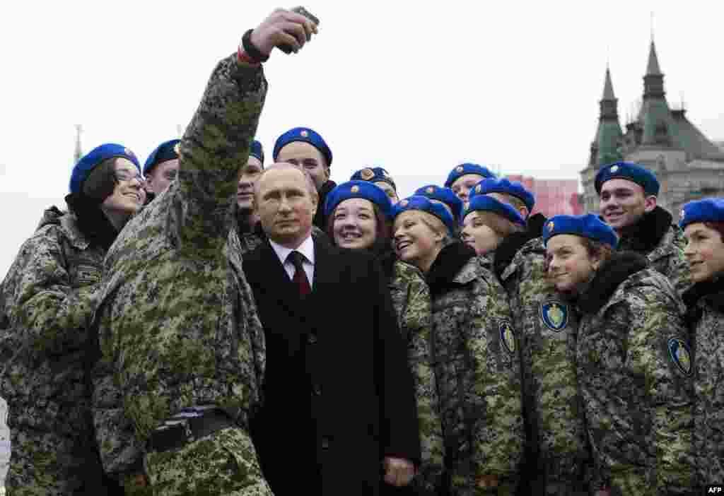 Russian President Vladimir Putin (center) poses for a selfie with young activists on Red Square in Moscow on Russia's Day of National Unity on November 4. (AFP/Natalia Kolesnikova)