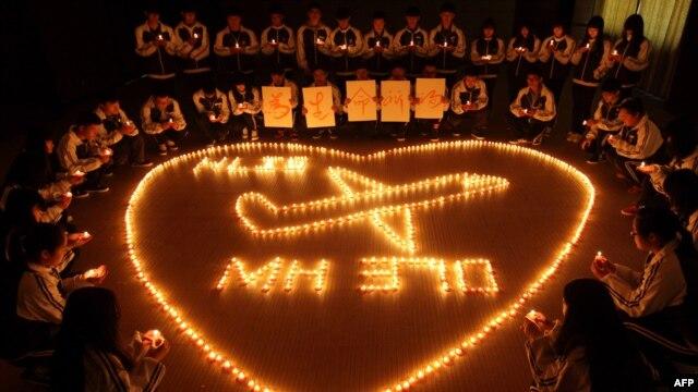 گروهی از دانشجویان در چین. طی روزهای گذشته بسیاری در مالزی و چین برای هواپیمای ناپدید شده شمع روشن کردند.